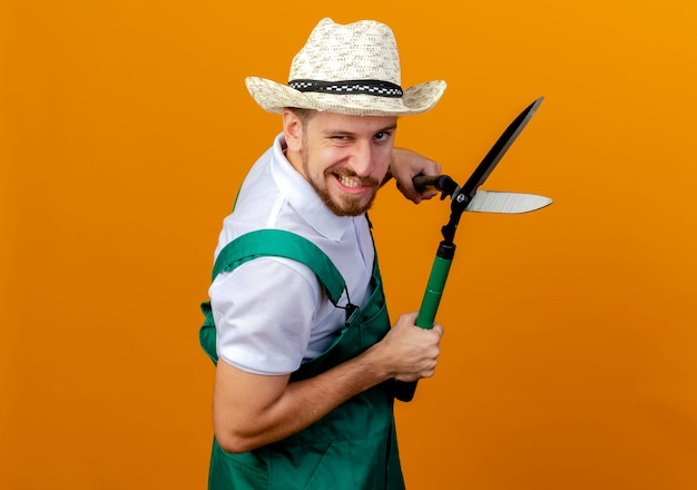 Zelfverzekerde jonge knappe slavische tuinman in uniform en hoed staande in profielweergave met snoeischaren op zoek geïsoleerd