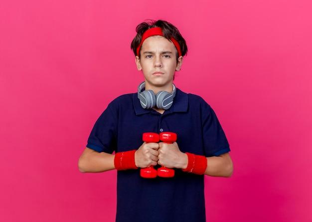 Zelfverzekerde jonge knappe sportieve jongen die hoofdband en polsbandjes en koptelefoon op de nek draagt met tandbeugels met halters kijken naar voorzijde geïsoleerd op karmozijnrode muur