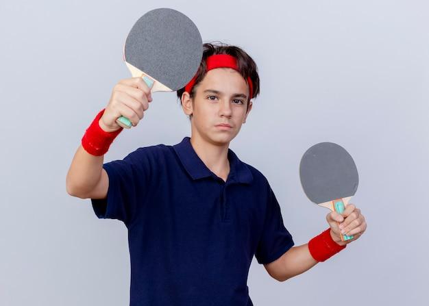 Zelfverzekerde jonge knappe sportieve jongen die hoofdband en polsbandjes met beugels draagt die naar de voorkant kijken, pingpongracket naar voren vasthouden en uitrekken op een witte muur