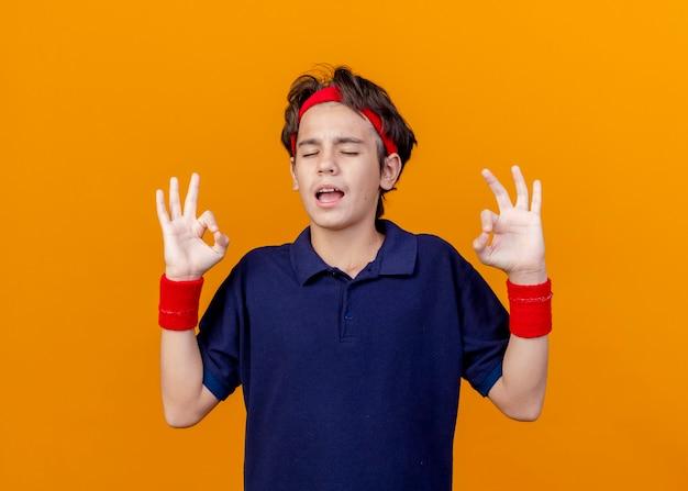 Zelfverzekerde jonge knappe sportieve jongen die hoofdband en polsbandjes met beugels draagt die ok teken met gesloten ogen doen die op oranje muur worden geïsoleerd