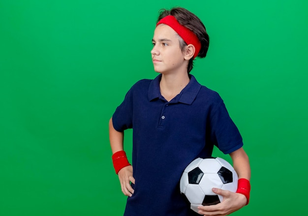 Zelfverzekerde jonge knappe sportieve jongen die hoofdband en polsbandjes met beugels draagt die voetbal houdt die hand op taille houdt die recht kijkt geïsoleerd op groene muur met exemplaarruimte