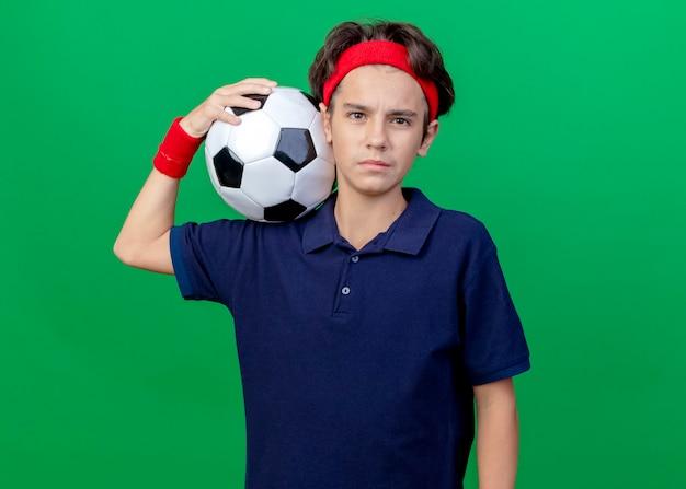 Zelfverzekerde jonge knappe sportieve jongen die hoofdband en polsbandjes met beugels draagt die voetbal op schouder houden die voorzijde bekijken die op groene muur wordt geïsoleerd