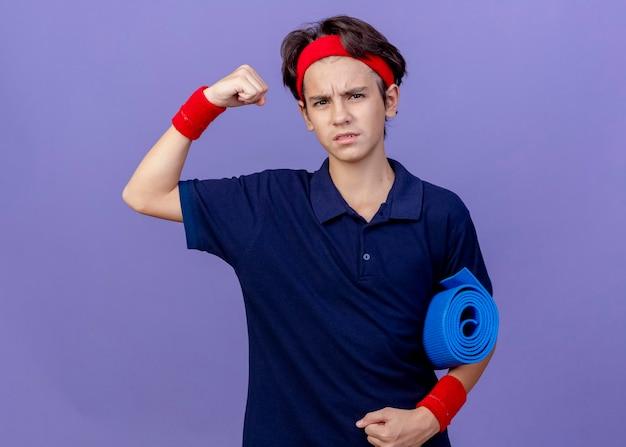 Zelfverzekerde jonge knappe sportieve jongen die hoofdband en polsbandjes met beugels draagt die yogamat houden die aan de voorkant kijken doet sterk gebaar geïsoleerd op paarse muur