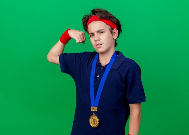 Zelfverzekerde jonge knappe sportieve jongen met hoofdband en polsbandjes en medaille rond de nek met beugels kijken naar voorkant doen sterk gebaar geïsoleerd op groene muur