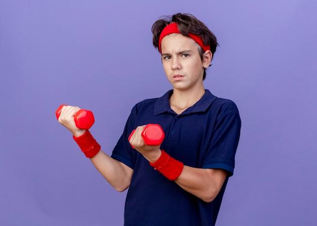 Zelfverzekerde jonge knappe sportieve jongen met hoofdband en polsbandjes met beugels met halters geïsoleerd op paarse muur met kopie ruimte