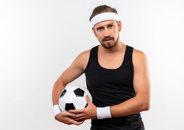 Zelfverzekerde jonge knappe sportieve man met een hoofdband en polsbandjes die voetbal vasthoudt en er geïsoleerd uitziet op een witte muur