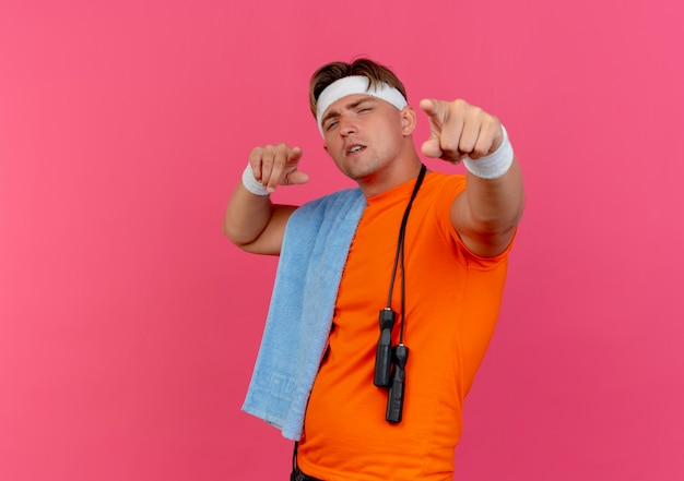 Zelfverzekerde jonge knappe sportieve man met handdoek om de nek en springtouw op schouder met hoofdband en polsbandjes wijzen geïsoleerd op roze met kopie ruimte