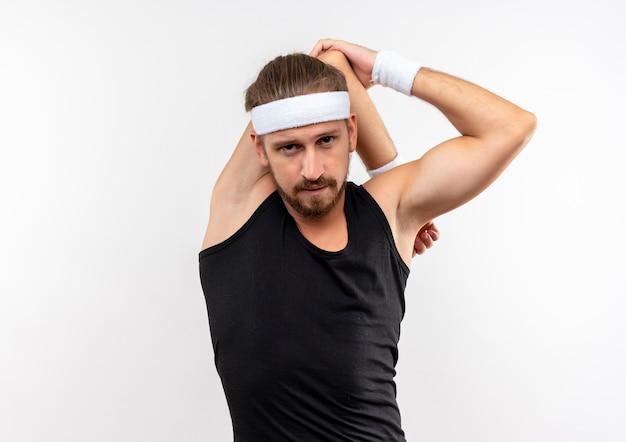 Zelfverzekerde jonge knappe sportieve man met hoofdband en polsbandjes die arm om het hoofd zetten en zijn elleboog geïsoleerd op een witte muur met kopieerruimte houden