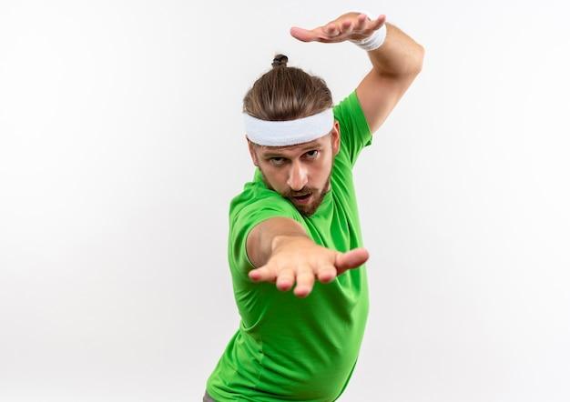 Zelfverzekerde jonge knappe sportieve man met hoofdband en polsbandjes die de hand boven het hoofd houden en een andere uitstrekken die op een witte muur is geïsoleerd met kopieerruimte