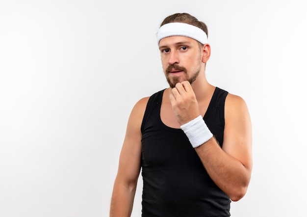 Zelfverzekerde jonge knappe sportieve man met hoofdband en polsbandjes die de hand op de kin zetten en op zoek geïsoleerd op een witte muur met kopieerruimte