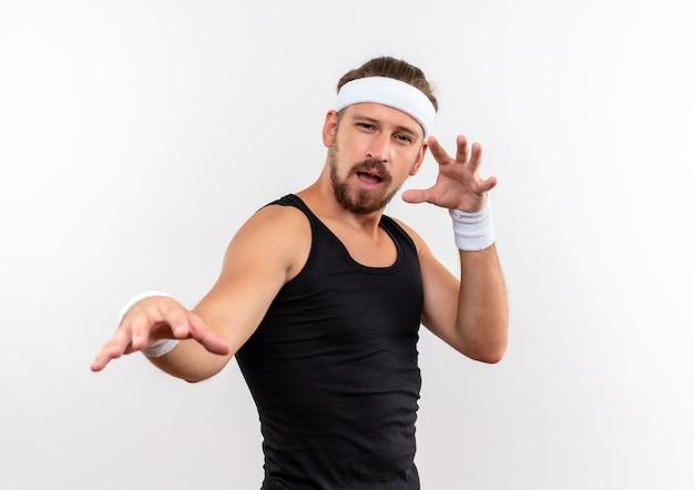 Zelfverzekerde jonge knappe sportieve man met hoofdband en polsbandjes die de hand uitstrekken en een andere in de buurt van het gezicht houden geïsoleerd op een witte muur