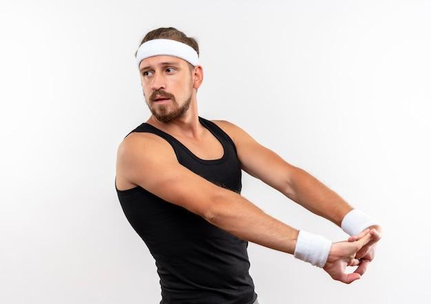 Zelfverzekerde jonge knappe sportieve man met hoofdband en polsbandjes die de handen uitstrekken en naar de zijkant kijken geïsoleerd op een witte muur met kopieerruimte