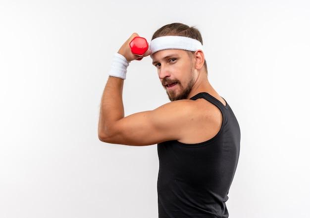 Zelfverzekerde jonge knappe sportieve man met hoofdband en polsbandjes die halter optilt die op een witte muur met kopieerruimte wordt geïsoleerd