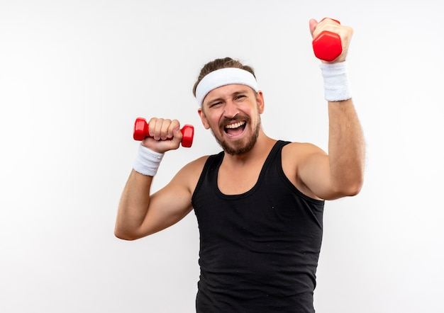 Zelfverzekerde jonge knappe sportieve man met hoofdband en polsbandjes die halters optillen die op een witte muur met kopieerruimte zijn geïsoleerd