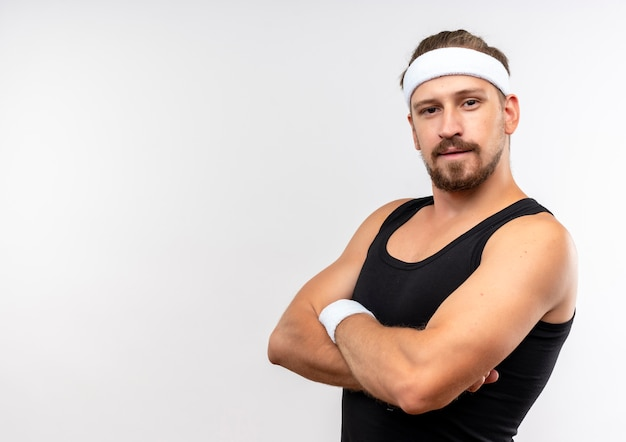 Zelfverzekerde jonge knappe sportieve man met hoofdband en polsbandjes die in gesloten houding staan en geïsoleerd op een witte muur met kopieerruimte kijken