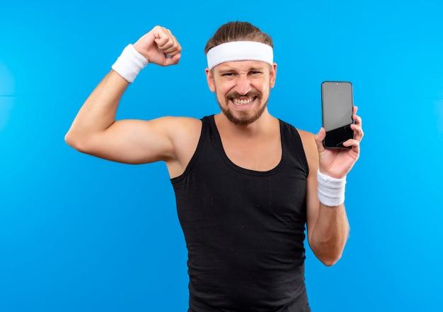 Zelfverzekerde jonge knappe sportieve man met hoofdband en polsbandjes die sterk gebaren en mobiele telefoon geïsoleerd op blauwe muur houden