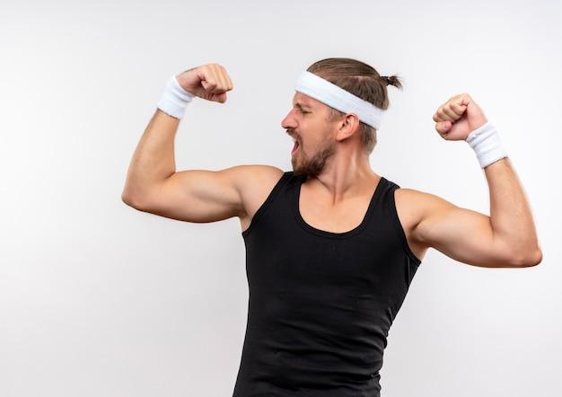 Zelfverzekerde jonge knappe sportieve man met hoofdband en polsbandjes die sterk gebaren en naar zijn spieren kijken die op een witte muur zijn geïsoleerd