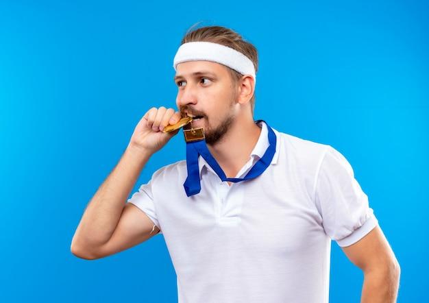 Zelfverzekerde jonge knappe sportieve man met hoofdband en polsbandjes en medaille om de nek, medaille vasthoudend en bijtend en kijkend naar kant geïsoleerd op blauwe muur