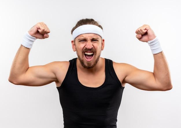 Zelfverzekerde jonge knappe sportieve man met hoofdband en polsbandjes gebaren sterk geïsoleerd op een witte muur