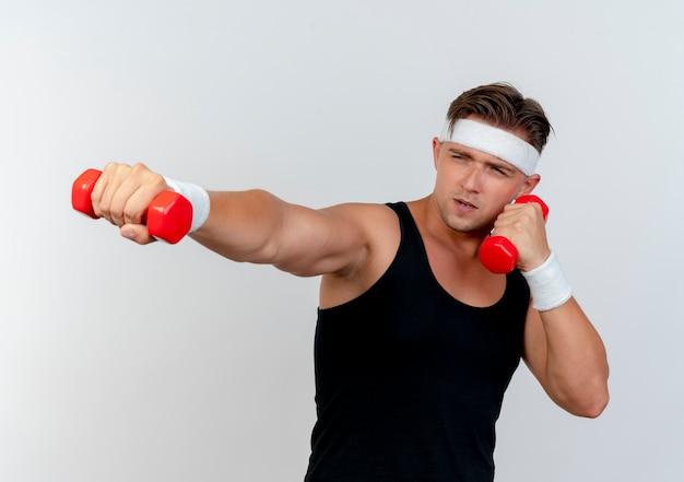 Zelfverzekerde jonge knappe sportieve man met hoofdband en polsbandjes houden en strekken halters kijken kant geïsoleerd op wit