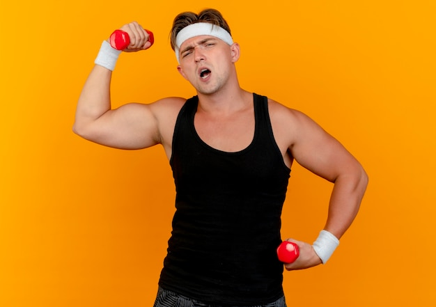 Zelfverzekerde jonge knappe sportieve man met hoofdband en polsbandjes houden en verhogen van halters geïsoleerd op oranje