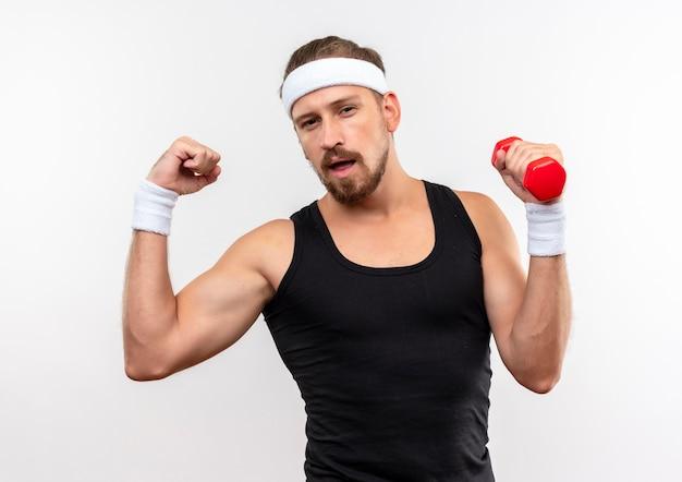 Zelfverzekerde jonge knappe sportieve man met hoofdband en polsbandjes met halter en gebaren sterk geïsoleerd op een witte muur