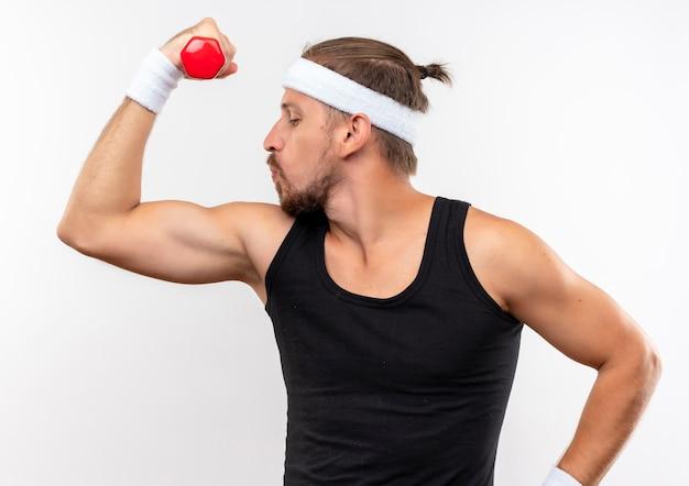 Zelfverzekerde jonge knappe sportieve man met hoofdband en polsbandjes met halter en sterke gebaren en kijkend naar zijn spieren geïsoleerd op een witte muur