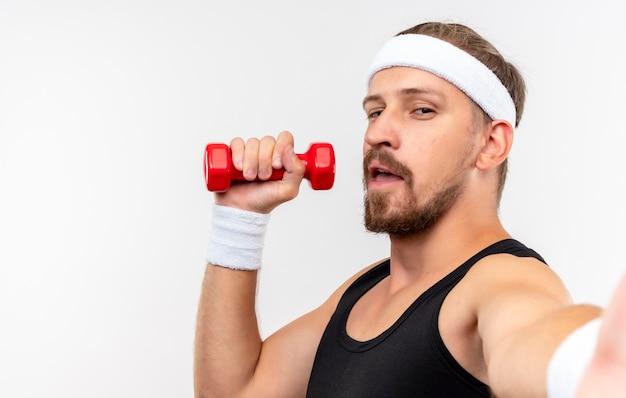 Zelfverzekerde jonge knappe sportieve man met hoofdband en polsbandjes met halter en strekkende hand geïsoleerd op een witte muur met kopieerruimte