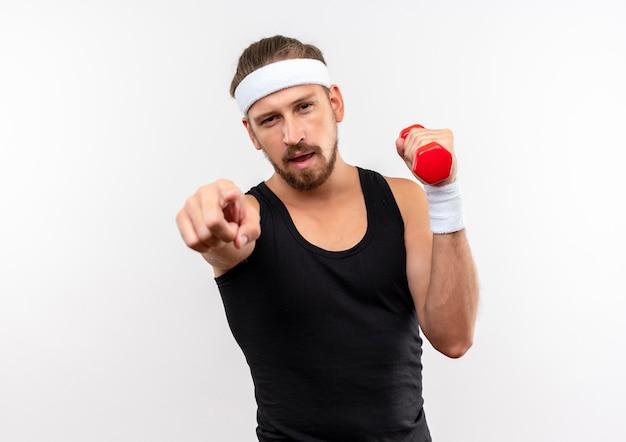 Zelfverzekerde jonge knappe sportieve man met hoofdband en polsbandjes met halter en wijzend geïsoleerd op een witte muur