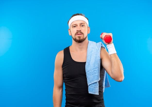 Zelfverzekerde jonge knappe sportieve man met hoofdband en polsbandjes met halter met handdoek op zijn schouder geïsoleerd op blauwe muur met kopieerruimte