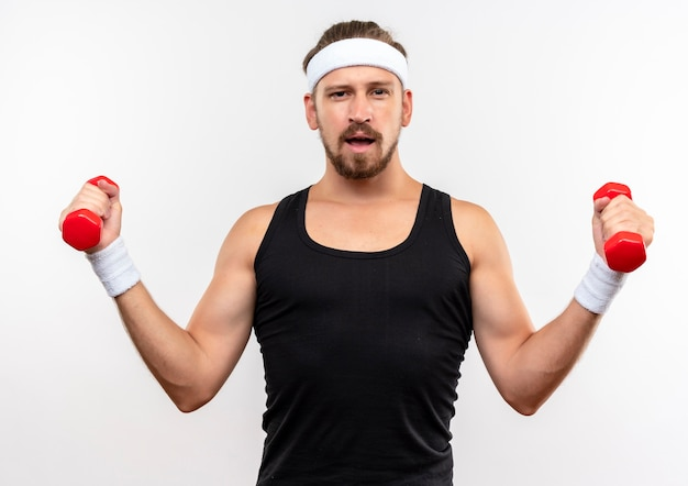 Zelfverzekerde jonge knappe sportieve man met hoofdband en polsbandjes met halters die geïsoleerd op een witte muur kijken