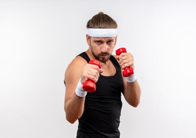 Zelfverzekerde jonge knappe sportieve man met hoofdband en polsbandjes met halters geïsoleerd op een witte muur