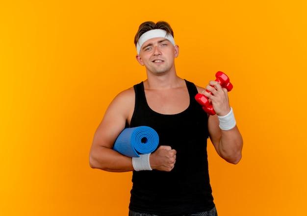 Zelfverzekerde jonge knappe sportieve man met hoofdband en polsbandjes met halters met handdoek geïsoleerd op oranje met kopie ruimte