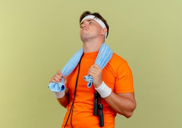 Zelfverzekerde jonge knappe sportieve man met hoofdband en polsbandjes met handdoek en springtouw rond de nek met handdoek op zoek recht geïsoleerd op olijfgroen met kopie ruimte