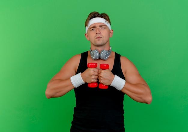 Zelfverzekerde jonge knappe sportieve man met hoofdband en polsbandjes met koptelefoon op nek houden halters geïsoleerd op groen