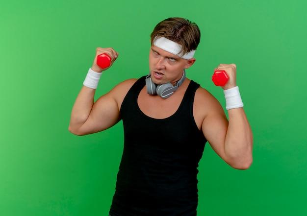 Zelfverzekerde jonge knappe sportieve man met hoofdband en polsbandjes met koptelefoon op nek houden halters op zoek rechtdoor geïsoleerd op groen