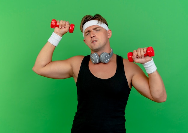 Zelfverzekerde jonge knappe sportieve man met hoofdband en polsbandjes met koptelefoon op nek verhogen halters geïsoleerd op groen