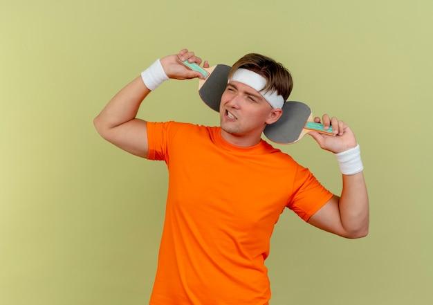 Zelfverzekerde jonge knappe sportieve man met hoofdband en polsbandjes met pingpongrackets achter hoofd kijken naar kant geïsoleerd op olijfgroen