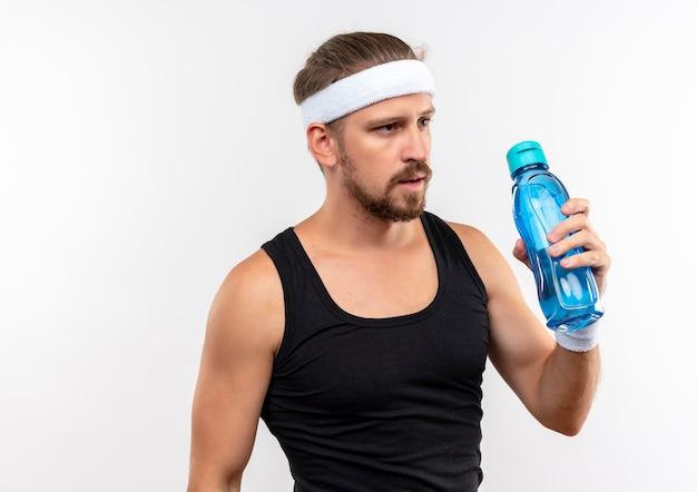 Zelfverzekerde jonge knappe sportieve man met hoofdband en polsbandjes met waterfles geïsoleerd op een witte muur