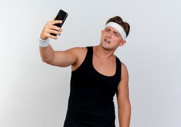 Zelfverzekerde jonge knappe sportieve man met hoofdband en polsbandjes nemen selfie geïsoleerd op wit