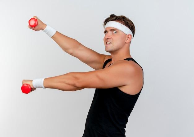 Zelfverzekerde jonge knappe sportieve man met hoofdband en polsbandjes staande in profiel te bekijken uitrekkende halters geïsoleerd op wit
