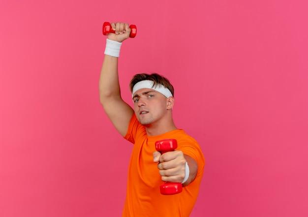 Zelfverzekerde jonge knappe sportieve man met hoofdband en polsbandjes verhogen en uitrekken van halters geïsoleerd op roze met kopie ruimte