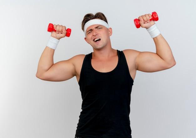 Zelfverzekerde jonge knappe sportieve man met hoofdband en polsbandjes verhogen halters geïsoleerd op wit