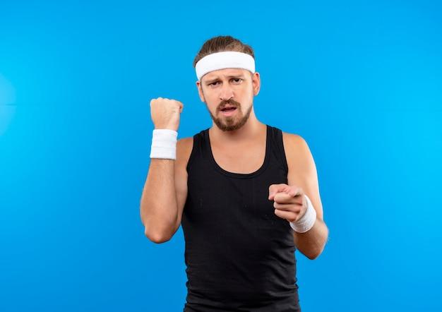 Zelfverzekerde jonge knappe sportieve man met hoofdband en polsbandjes, vuist balde en wijzend geïsoleerd op blauwe muur met kopieerruimte