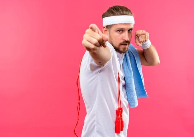Zelfverzekerde jonge knappe sportieve man met hoofdband en polsbandjes wijzend met springtouw en handdoek op schouders geïsoleerd op roze muur met kopieerruimte