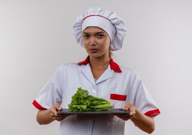 Zelfverzekerde jonge kok vrouwelijke dragen chef-kok uniform bedrijf sald op snijplank op geïsoleerde witte muur