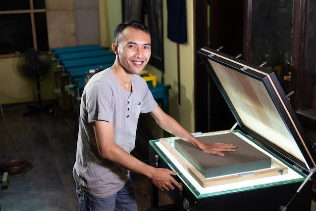 Zelfverzekerde jonge man aan het werk om een spons in te drukken om film op zeefdrukoppervlak voor te bereiden