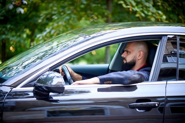 Zelfverzekerde jonge man besturen van een auto.
