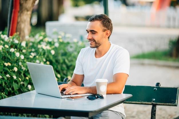 Zelfverzekerde jonge man die op laptop werkt terwijl hij buiten aan de houten tafel zit