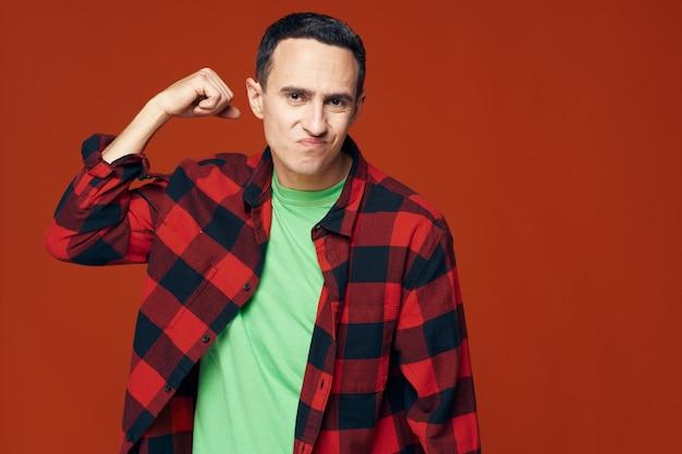 Zelfverzekerde jonge man in een overhemd en in een groen t-shirt